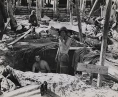 """""""The Lousy Lousy Lounge,"""" Tarawa, November 1943  """"Home is Where You Find It-The fighting qualities of the Marines is well known but their sense of humor is running a good second. Their humor coupled with their adaptability to make the best of an impossible situation is demonstrated by these two Marines on Tarawa who have named their dugout """"The Lousy Lousy Lounge."""""""""""