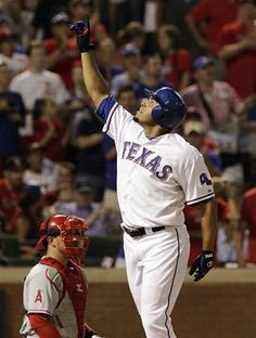 Texas Rangers' Nelson Cruz, right, points to the sky at home plate in front of Los Angeles Angels catcher Bobby Wilson after Cruz's solo home run during the fourth inning of a baseball game, Thursday, Aug. 2, 2012, in Arlington, Texas. The Rangers won 15-9.  (AP Photo/LM Otero)