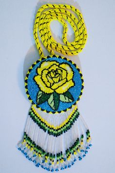 3 1/2 inch diameter beaded rosette with yellow rose design hung on beaded chain. Yellow, black, blue, dark and light green size 11* seed beads. #0425