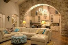 stone wall with arch dividing living room and kitchen