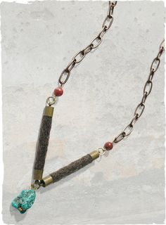 The Taos Necklace is a mixed-media assemblage of brass chains, felted wool and rough-cut turquoise.