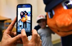 Andrew Marinelli snaps a photo of his son, Joseph with Otto the Orange during a visit to the Solvay Library in Solvay, N.Y., Wednesday, July 8, 2015.
