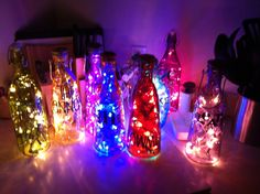 Gift idea: Christmas lights in a bottle/scrapbook lettering for names for outside You will Need:  1) a strand of lights (25-30 mini lights are best) 2) glass wine style bottle  3) drill & glass/ tile drill bit (for making hole in back) for plug to run through 4) adhesive lettering or hot glue 5) gems for decorating