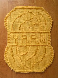 """Free Knitting Pattern for Yarn Cloth - Skein-shaped cloth with YARN on the band. The cloth is about 8"""" x 11"""", so it could also be used as a towel, placemat or doily. Designed by Theresa Jones"""