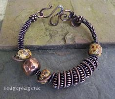 On a heavy gauge solid copper wire core, tiny coiled copper wire loops its way around the bracelet, creating a pleasing visual journey. The earthy artisan lampwork beads were created by Jillian Tonge (Etsy's Jillerydesigns). The solid copper hammered bead was hand forged by me. A dark rich patina enhances this bracelet's richly textured design.