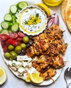 This looks like the ultimate platter of deliciousness 😍Preserved lemon chicken skewers, lemon dill yogurt sauce with crunchy cucumber, creamy feta, buttery olives & sweet cherry tomatoes (via Cheesecake Cupcakes, Antipasto, Taziki Sauce, New York Times Cooking, Feta, Boneless Skinless Chicken Thighs, Chicken Breasts, Preserved Lemons, Braised Chicken