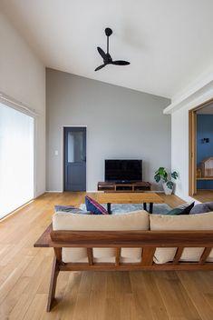 勾配天井を配した開放的なリビング空間。グレー色のアクセントクロス部分の無垢材の建具は、ディープグレー色に塗装し、空間にほどよいアクセントを添えました。