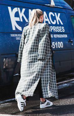 Foto de street style com maxi casaco de estampa gráfica e tênis adidas superstar branco