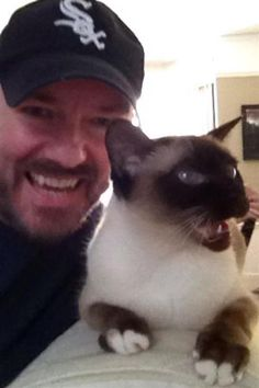"""Ricky Gervais may be the king of dark and awkward comedy but when it comes to his cat Ollie, Ricky is a total softie. He often tweets about his gorgeous Siamese (sample post: """"Ollie is curled up so tight, she looks like a little germinating seed""""), who was a gift from U.K. talk show host Jonathan Ross. Ricky also likes to spend as much time as he can with the fur ball. """"My evening usually consists of sitting on couch in my pajamas from 6 p.m. with the cat on my lap watching trash TV,"""" Ricky…"""