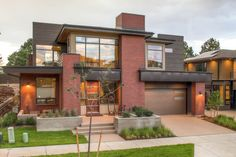 The very modern exterior of the home features red brick and dark brown wood siding that make the boxy design feel welcoming.