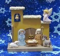 Pesebre navideño con botones pegados sobre casita de madera, con campanita