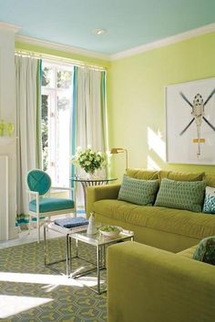 Timothy MatherGreen walls with turquoise blue ceiling, white drapes with blue/green ribbon trim, velvet green sofa & chair with blue pillows, French turquoise blue chair, chrome accent tables and gray yellow rug!