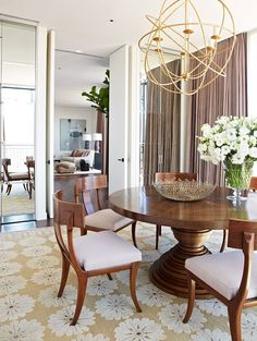 Orbital chandelier + stacked pedestal table + flowered rug  Love it but I don't know who it's by.  Love the chairs.  Great nod to mid-century modern that would still fit with my decor.