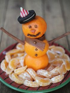 Snowman Fruit Snack - Here's a fruit snack that could make for a fun change-up to Santa's usual cookie platter, or even a neat Christmas morning display!  Halos mandarins serve as the focal point for this cute little tray of sweetness. Use a skewer to stack them three high for a snowman fruit snack...