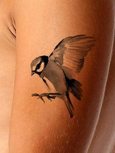 This bird in flight, realistic watercolor tattoo is beautifully rendered. This bird tattoo serves as a symbol of love and fortune, looks stunning on the skin and is available as both a black and color