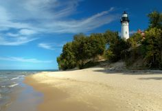 White lighthouse tower behind trees on a sandy beach at Pictured Rocks National Lakeshore