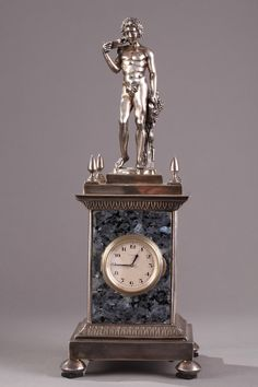 Silver and granite mantel clock topped with a young, nude Bacchus and Satyr.