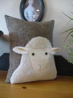 This is another sheep pillow that Ive designed! Hes just as cute as can. Hes nice and woolly and his ears stick off the pillow for a 3 dimensional look. Hes even got little eyelashes. Inspired by a sheep photograph as are many of my lamb and sheep pillows. Stitched onto a black, grey, cream mix wool fabric. This pillow is stuffed with polyester fiberfill and measures 9 x 11. Comes from a pet and smoke free home.
