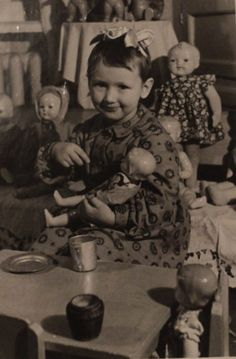 Vintage photo of a little girl surrounded by dolls.