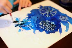 I then used my trusty hot glue gun to trace the snowflakes from the template in hot glue. add salt (it bleaches out parts of the watercolor and makes an interesting pattern if you haven't tried it before).  To have the salt work correctly, your painting needs to have a thin layer of moisture over it.