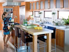 Eye-level windows make this beachfront kitchen reminiscent of a boat galley. Wood cabinetry with frosted glass and cubic handles, stainless steel appliances, and clean-lined barstools make it a modern, useful kitchen.