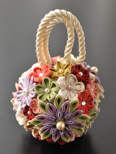 Learning how to make kanzashi flowers, i will make something like this one day. Good idea for temari.