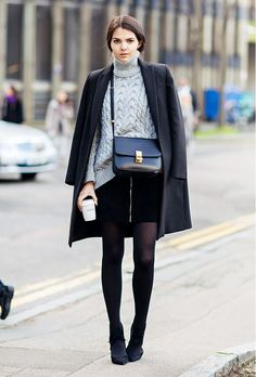 A turtleneck sweater is worn with a black skirt, a black jacket and a black crossbody.
