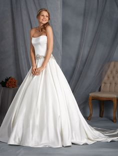 Style 2541  Strapless Satin ball gown with a scooped neckline, crystal buttons and a dropped waistline that has been encrusted with crystal beading, rhinestones and metallic beads. The full circular skit has been accented with side seam pockets and a chapel length train. MY FAVORITE DRESS.... XO