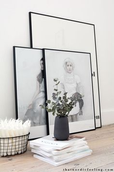 white walls, white candles, simple contemporary prints in black frames and bleached floorboards. Beautiful