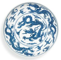 A rare blue and white 'dragon' dish, Mark and period of Jiajing. Estimate 400,000 — 600,000 HKD ( 45,157 — 67,735 EUR). Lot Sold 3,680,000 HKD (415,441 EUR). Photo: Sotheby's.  the shallow rounded sides supported on a tapered foot, vividly painted to the interior in cobalt-blue with a central medallion enclosing a five-clawed dragon writhing amongst stylised cloud scrolls, its sinuous scaly body with muscular legs terminating in sharp claws, encircled by a pair of five-clawed dragons…