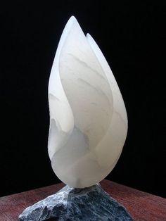 Gemaakt door: Jan van der Laan. Het is een organische vorm. De steen is volledig gepoleist. Ik vind de vorm heel mooi, omdat je heel goed ziet dat het 3D is. De kleur past erbij. De steen die er onder staat geeft een mooi contrast met de steen die er op staat. Je ziet de groei van het beeld in de vorm.