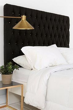 Add instant grown-up elegance to your bedroom with a tufted headboard. This charcoal one from Urban Outfitters features brass buttons and is a definite statement piece. Go simple with your accessories: a clean lined side table, and a retro mid-century modern brass bedside sconce lamp and white linens are all you need to complete this look.