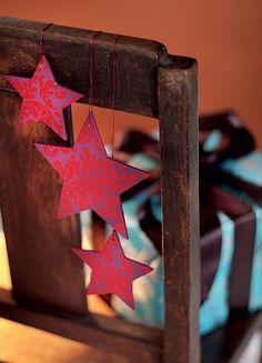 Pendurar estrelas coloridas, feitas de papel mesmo, no encosto das cadeiras é o tipo de detalhe ultrassimples que faz a diferença em um jantar