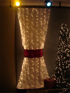Kevin Crainshaw fromSt. Johns Presbyterian ChurchinJacksonville, FL brings us these glittery Christmas curtains.Quite simply, they bought some translucent white fabric and put white Christmas lights behind it. They wrapped it with a red sash to give the white fabric its shape. Then they added trees with Christmas lights in between the fabric curtains.They added some Christmas gifts around the room to add more Christmas flare.