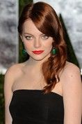 Emma Stone with 1940s loose waves, bright red lips and green earrings that match her eyes and contrast with her classic simple black dress.