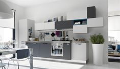 What a fun design! The #modular #cabinetry in white and gray are stacked asymmetrically - adding tons of visual interest to this chic, modern kitchen.  Notice how the single dash of blue keeps your focus anchored to this dazzling cabinetry?