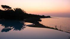 Sunrise over the amazing infinity pool in the private beach at hotel costa dei fiori, on the south coast of Sardinia.