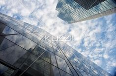 reflection on tall office buildings. - Low angle shot of reflection on tall commercial buildings against cloudy sky.