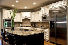 White cabinets, black island, granite countertop.