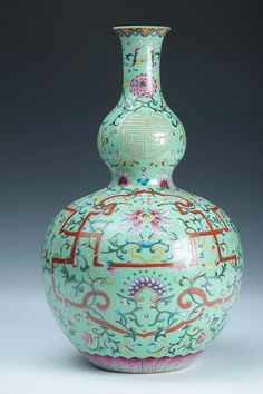 CHINESE FAMILLE ROSE PORCELAIN GU-FORM VASE, Qianlong iron red seal mark. Floral decoration on incised apple green decoration, turquoise interior and foot. - 16 in. high.
