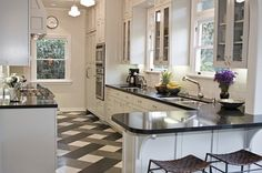 Kitchen after remodeling by Newman & Wolen Design with glass cabinets, black quartz counter tops, stainless appliances and a grey and white plaid floor