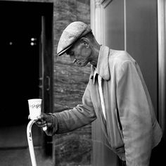 An emaciated man in a cap bending slightly forward while carrying a cup and a white cane. Undated, Chicago, IL