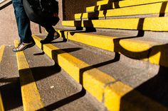 Stepping : A man walks down some yellow stairs, exiting a hospital in this street photograph from Toronto.