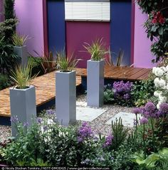 The French aesthetic meets a modern sensibility. The gray and lilac tones highlight the French planting selections like Allium and lavender, while the clean lines and wooden catwalk suggest a modern landscape design style. Photo by Nicola Stocken Tomkins.