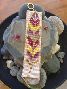 This beaded bracelet is the second in my Painted Feather series. It features 15 different shades, including a background of Pearl Ceylon. The outline and edging is woven in gold-plated seed beads. Colors in the feather itself include green gold. Loom Bracelet Patterns, Bead Loom Bracelets, Bead Loom Patterns, Jewelry Patterns, Beading Patterns, Beading Ideas, Native Beadwork, Native American Beadwork, Loom Bands