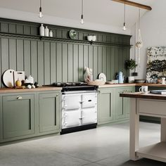 Green is a huge kitchen trend and one way to mirror this is by statement kitchen cabinets. We love how bright the white AGA R3 Series looks next to the green tones.  The AGA R3 Series is one of the newest AGA models and is ideal for those who love the original – on all the time – AGA, but want added functionality and to save money on running costs. It runs solely on a 13-amp electricity supply, requiring no servicing, no plinth and no flue.  This paint is Green Smoke by Farrow and Ball. Aga Kitchen, Green Kitchen Designs, Contemporary Kitchen, Kitchen Design, Aga Stove, Modern Kitchen, Kitchen Cabinetry, Kitchen Cabinets, Aga Cooker