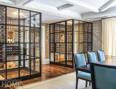 Glass and iron wine cellars are the focal point of this Connecticut dining room . Interior design by Hollester Interiors, Architecture by Vincent Burin Architects, Photography by Nat Rea