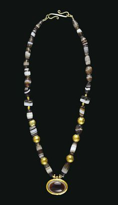 A ROMAN GOLD AND BANDED AGATE NECKLACE  CIRCA 2ND-3RD CENTURY A.D.  Composed of barrel-shaped, cylindrical and tabular banded agate beads, interspersed with gold spherical beads, centered by an oval pendant in the form of a gold box set with a convex eye agate, the box with a flanged rim, three suspension loops below for now missing elements; strung with a modern S-hook closure