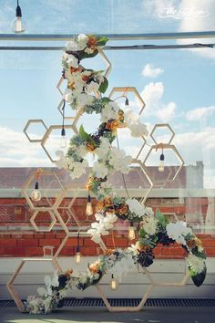 floral installation and large string lights wrapped around wooden hexagon structure