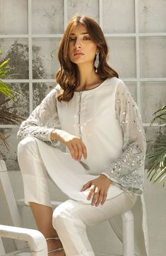The perfect party dress. This classic white salwar kameez is detailed with silver tilla and mirror work along the sleeves. Crystal buttons and silver edging along every seam of the tunic add the finis Simple Pakistani Dresses, Pakistani Fashion Casual, Pakistani Wedding Outfits, Pakistani Dress Design, Pakistani Bridal, Pakistani White Dress, Stylish Dresses For Girls, Simple Dresses, Casual Dresses
